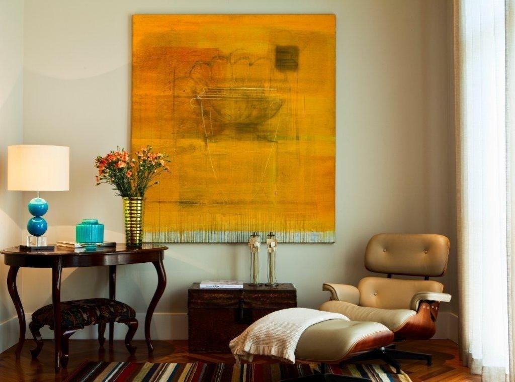 Outro ângulo do living, com um espaço para leitura, onde o destaque é uma poltrona Charles & Ray Eames, revestida em couro (Clami Design). Como apoio, a mesa de madeira cria contraste com o design mais clássico. O projeto de decoração da Casa no Alto de Pinheiros é assinado por Marília Veiga