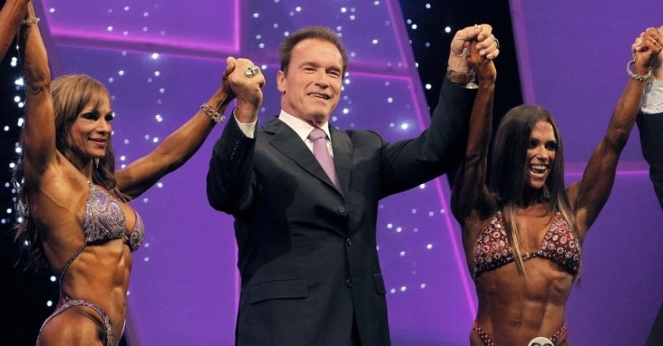 Arnold Schwarzenegger (dir.), estrela de consagrados filmes de ação e ex-governador da Califórnia, parabeniza duas participantes na entrega dos prêmios da segunda edição do Arnold Classic Europe