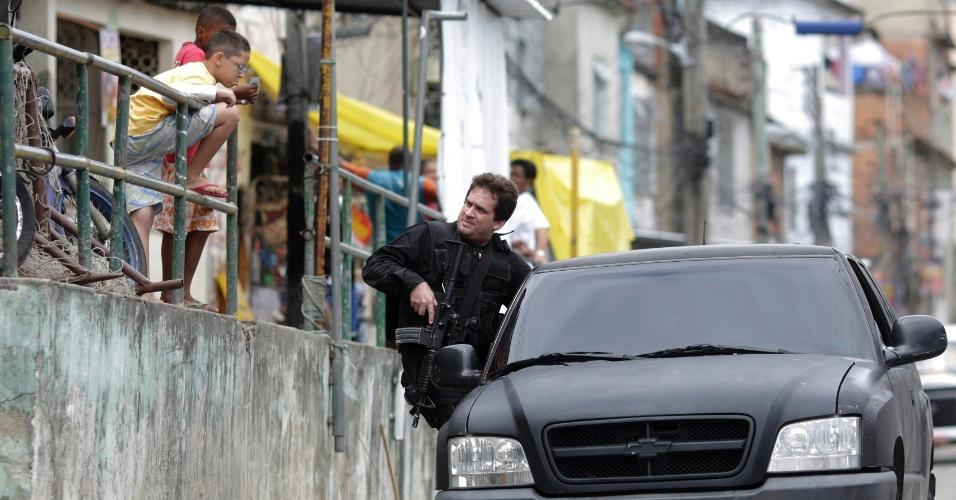 14.out.2012 - Garoto observa ação de policial civil na favela do Jacarezinho, na zona norte do Rio de Janeiro (RJ), realizada paralelamente à ocupação das favelas do Complexo de Manguinhos (comunidade vizinha)