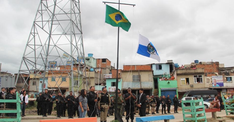 14.out.2012 - Policiais observam bandeiras do Brasil e do Estado do Rio serem hasteadas em uma praça do Complexo de Manguinhos, na zona norte da capital, em reconhecimento à ocupação da comunidade