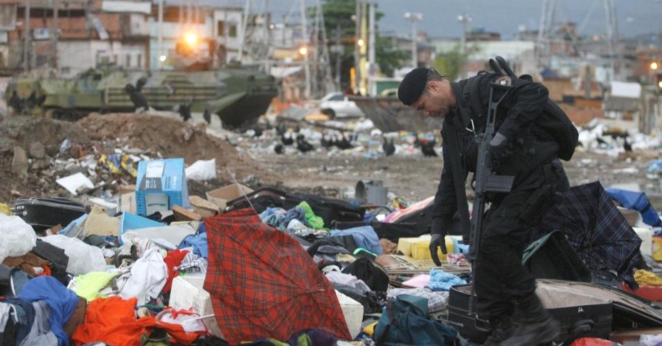 14.out.2012 - Policial do Bope (Batalhões de Operações Policiais Especiais) faz busca em meio a entulhos em favela do Complexo de Manguinhos, na zona norte do Rio de Janeiro, durante o processo de ocupação da comunidade para dar início a instalação de UPPs (Unidades de Polícia Pacificadora)