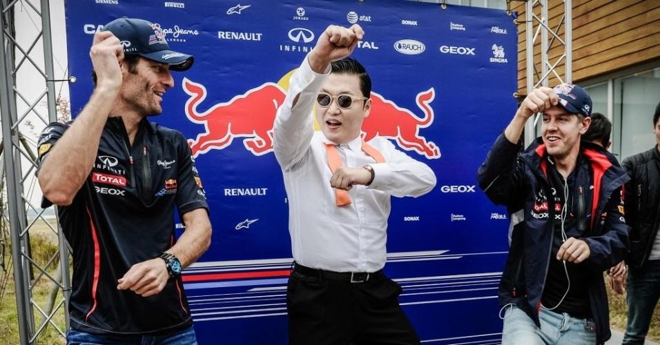 Pop star sul-coreano Psy ensina os pilotos da Red Bull Mark Webber (e) e Sebastian Vettel a dançar o hit