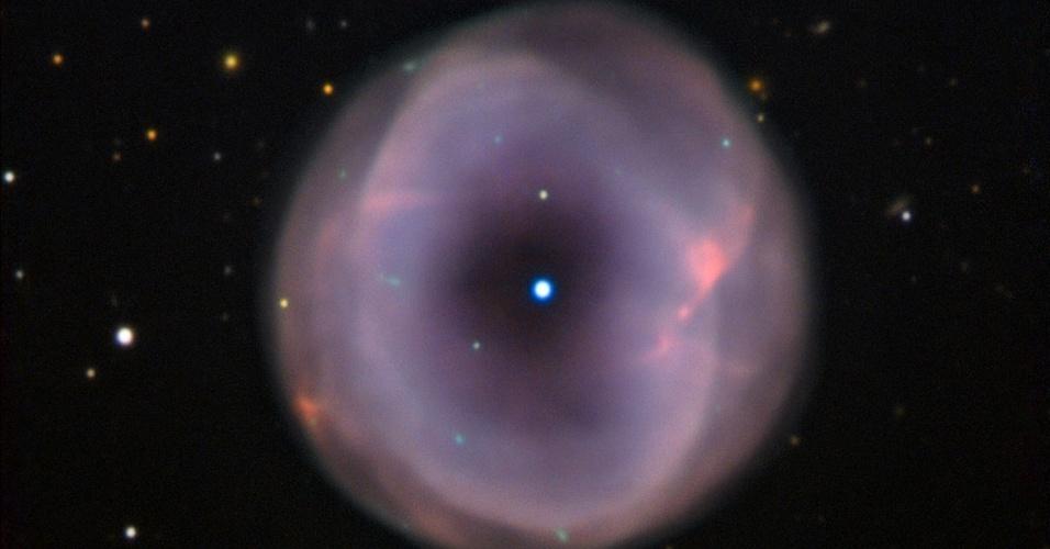 16.out.2012 - O Observatório Europeu do Sul (ESO, na sigla em inglês) divulga imagem mais precisa de uma nebulosa planetária que fica na constelação de Grou, a 3.000 anos-luz de distância da Terra. A IC 5148 cresce a 50 quilômetros por segundo, considerada uma das expansões mais rápidas do universo, e colore o universo - o gás e a poeira expelidos por uma estrela no fim da vida formam um arco em tom pastel ao seu redor