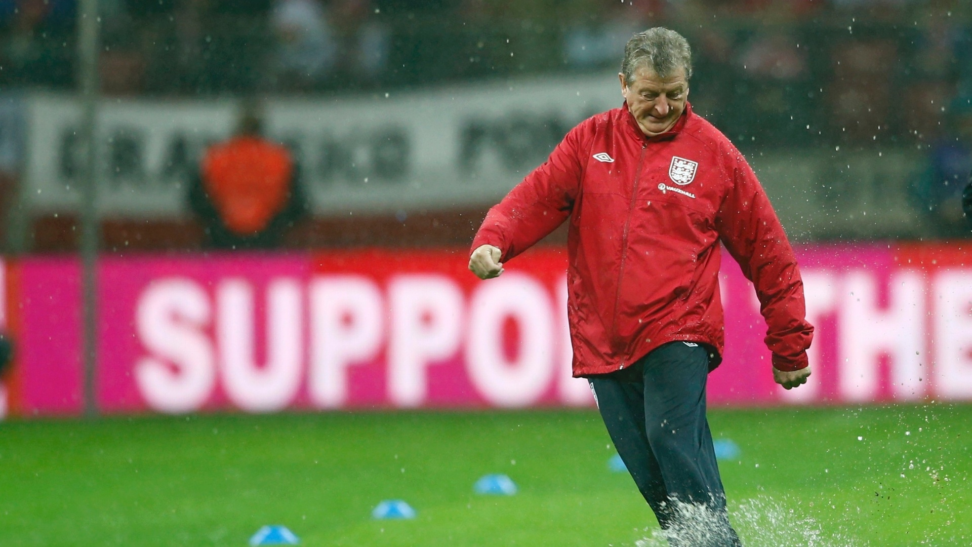 Roy Hodgson, tcnico da seleo da Inglaterra, tenta chutar uma bola no gramado encharcado do estdio de Varsvia, onde a equipe enfrentar a Polnia pelas eliminatrias
