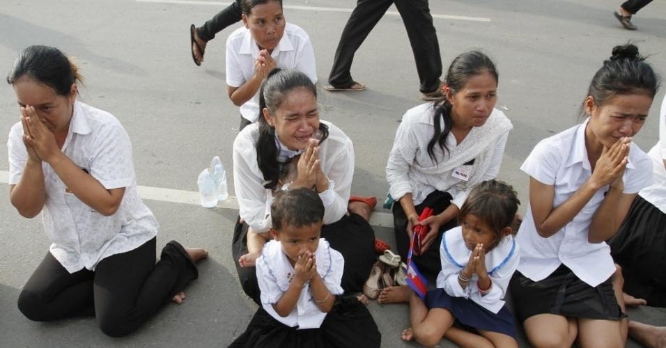 17.out.2012 - Mulheres e crianças choram durante passagem do cortejo fúnebre do ex-rei Norodom Sihanouk, morto aos 89 anos na segunda-feira (15), vítima de um ataque cardíaco