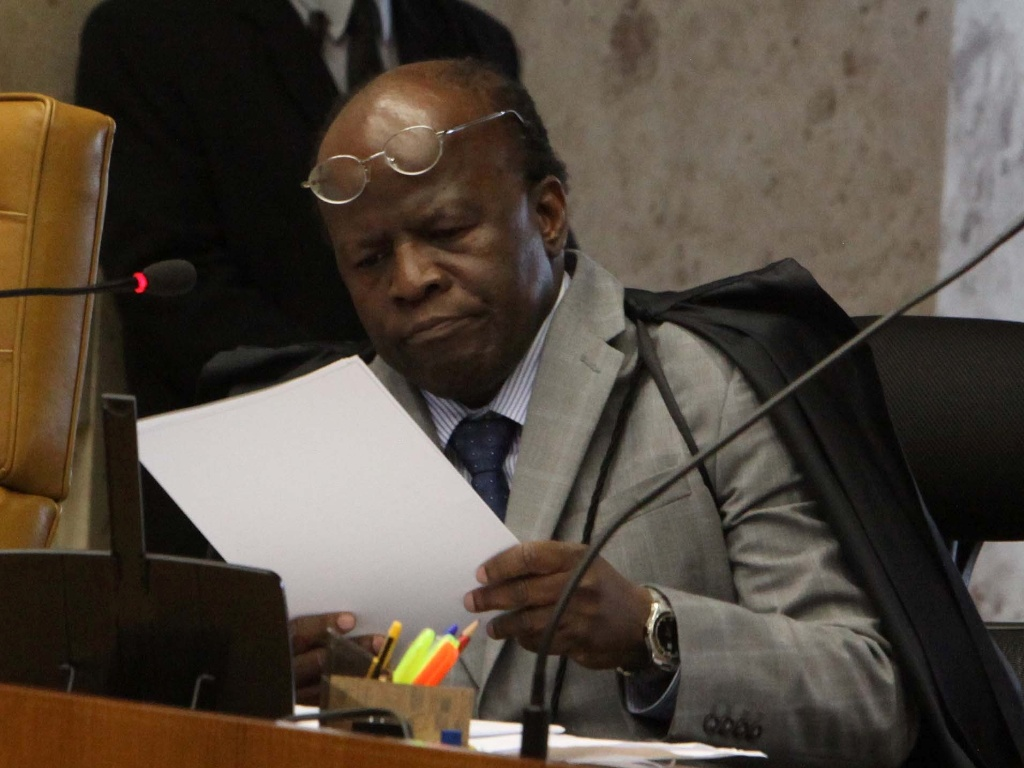 17.out.2012 - O ministro Joaquim Barbosa analisa processo na mesa do STF durante sesso do julgamento de ex-deputados do PT e ex-ministro por lavagem de dinheiro no STF, em Braslia