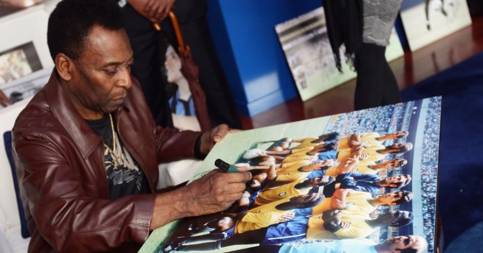 Pelé assina um pôster da seleção brasileira durante sua visita ao Museu dos Campeões; o Rei do futebol acompanhou a premiação Golden Foot 2012 (17/10/2012)