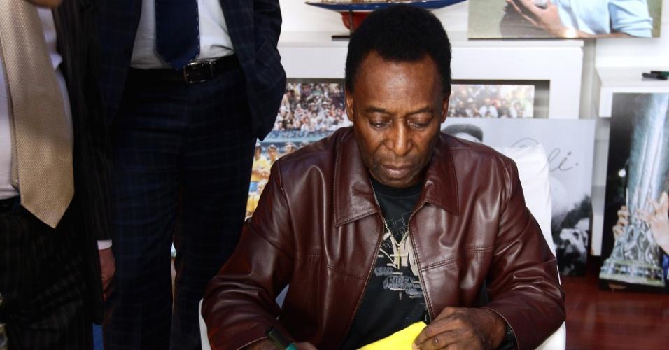 Pelé assina uma camisa da seleção brasileira durante sua visita ao Museu dos Campeões; o Rei do futebol acompanhou a premiação Golden Foot 2012 (17/10/2012)