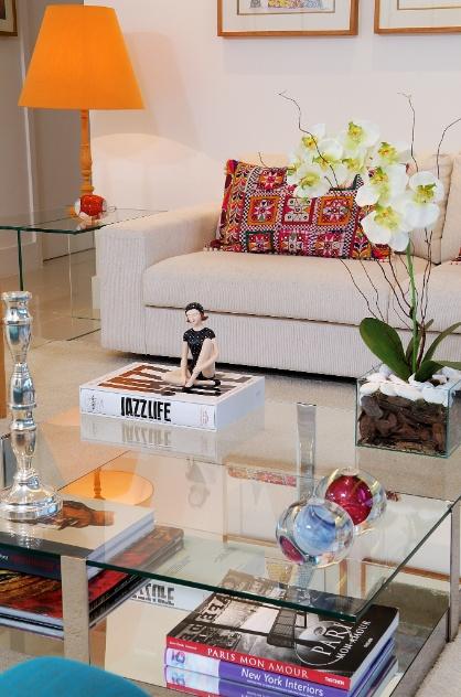 Na sala de estar do apartamento Lauria, projetado por Gabriel Magalhães e Luiz Claudio Souza, o abajur alaranjado é Omni Light e conduz o ritmo das cores do ambiente - apoiado sobre mesa Pi em vidro, com assinatura de Jacqueline Terpins. Além dele, as almofadas artesanais étnicas do Afeganistão (Marcelo Kruschewsky) pontuam de matizes fortes o espaço