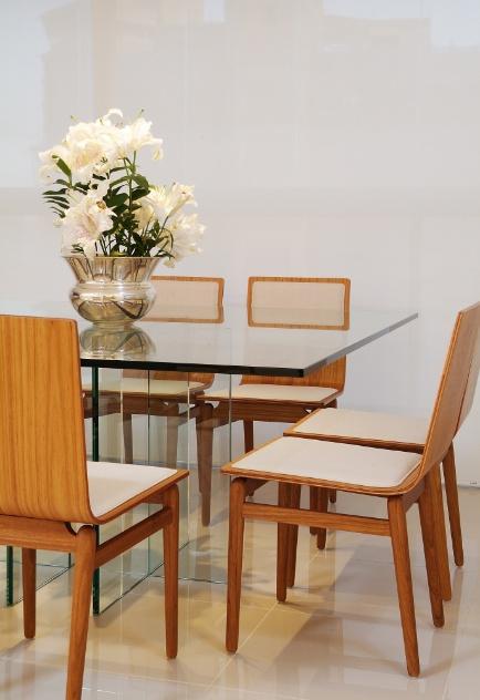 A mesa de jantar 14 Bis quadrada e para oito lugares é assinada por Jacqueline Terpins, com tampo em vidro transparente temperado e com 12 mm de espessura. As cadeiras Pompom têm design de Fernanda Brunoro (Home Design). Os móveis compõem a área de jantar do apartamento Lauria, com projeto de Gabriel Magalhães e Luiz Claudio Souza