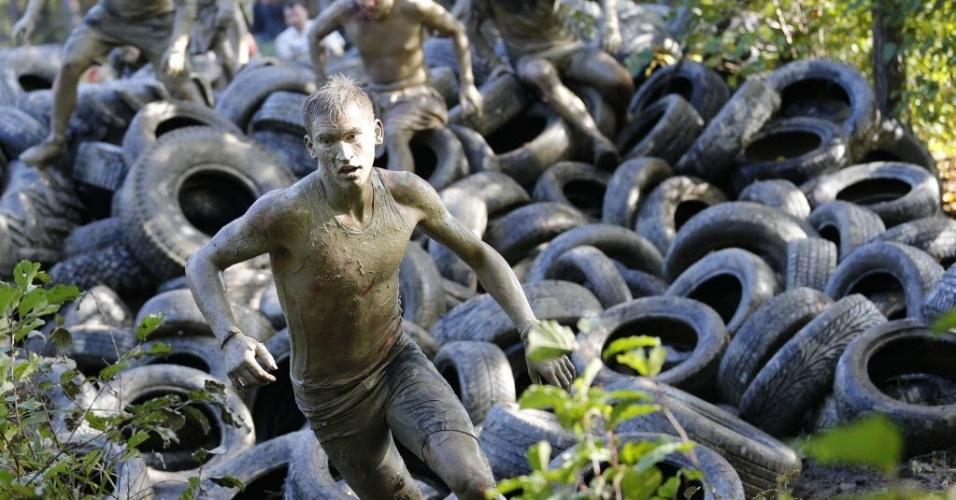 Competidores austríacos passam por obstáculos na prova de 50 km realizada na lama, uma tradição anual na região de Obertriesting