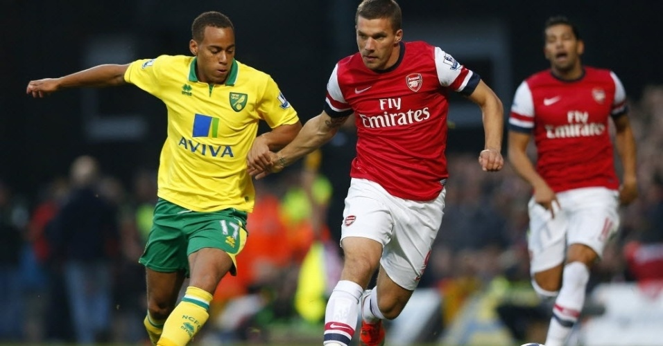 Lukas Podolski (dir.), do Arsenal, disputa a bola com Elliott Bennett, do Norwich City, em partida do Campeonato Inglês