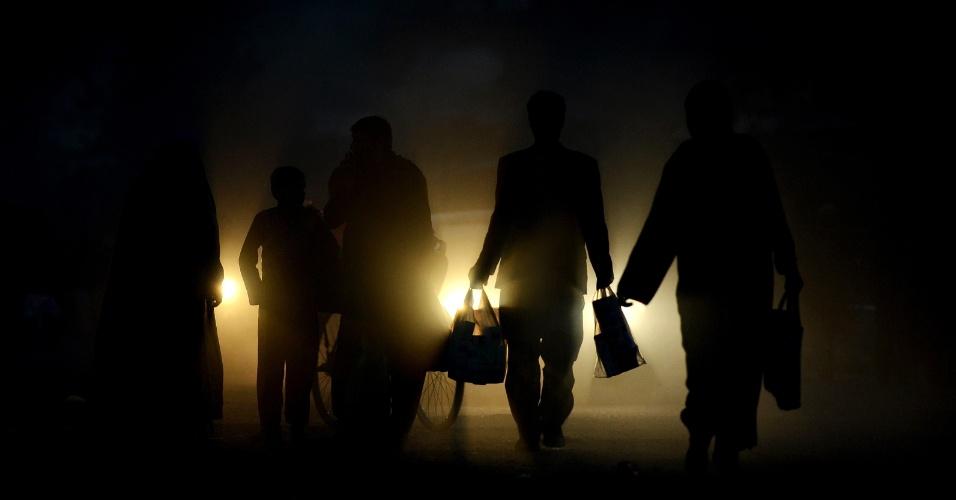 Silhuetas de pessoas caminham carregando sacolas, em rua com empoeirada do centro de Cabul, no Afeganistão