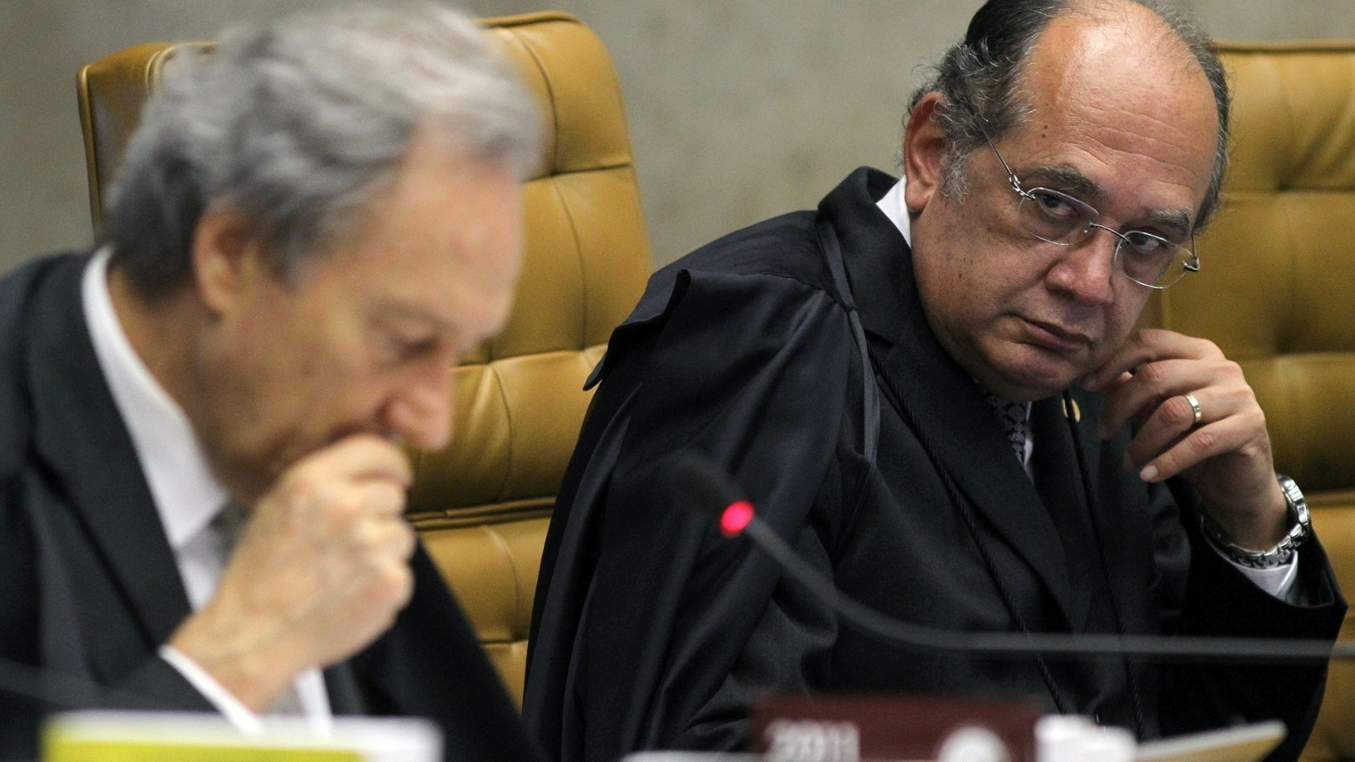 24.out.2012 - Em destaque, o ministro Gilmar Mendes observa o ministro-revisor Ricardo Lewandowski analisar o processo do julgamento do mensalo. Nesta quarta-feira, a maioria dos ministros do STF (Supremo Tribunal Federal) seguiu o revisor do processo e votou pela aplicao de uma pena de trs anos e um ms, alm de multa no valor de R$ 108 mil, para o publicitrio Marcos Valrio