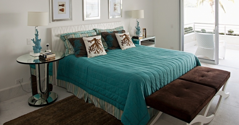 Em azul, branco e marrom, a suíte máster da Casa Tabatinga é pouco mobiliada, mas possui conforto. O ambiente de dormir é integrado a uma pequena sala, ao banheiro e ao closet, além de uma varanda agradável. O projeto da residência é da arquiteta Selma Tammaro