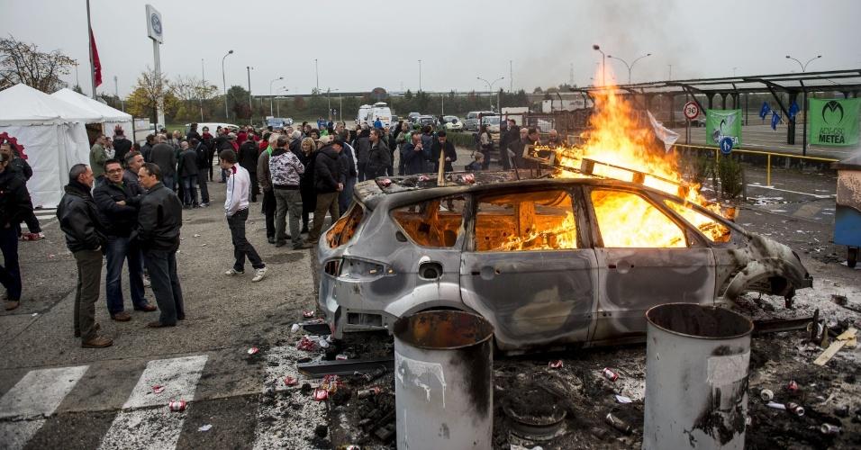 25.out.2012 - Funcionários da Syncreon, fornecedora de fábricas de automóveis, observam carro em chamas durante uma manifestação realizada em Genk, na Bélgica, contra plano de demissões. A Ford --um dos clientes da empresa-- anunciou o fechamento da fábrica de Genk, ameaçando 4.300 empregos