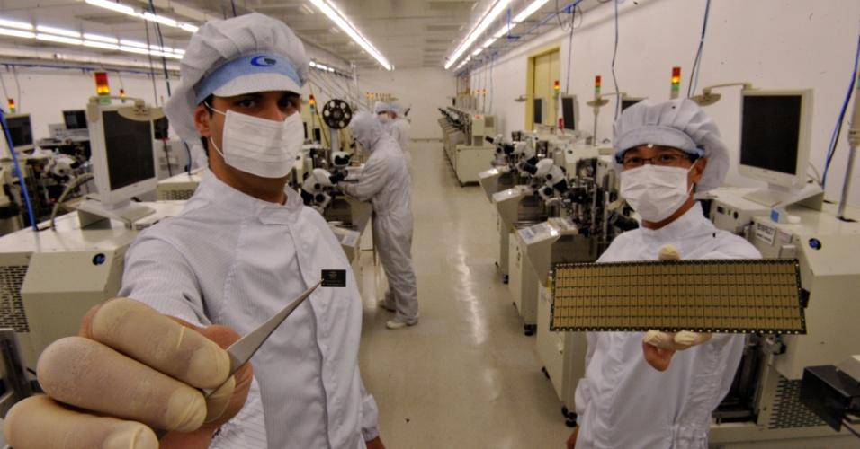 25.out.2012 - Funcionários de fábrica de chips de São Leopoldo (RS), no Vale dos Sinos,  mostram modelos de cartões de memória que deverão estar presentes em computadores vendidos no Natal. No próximo mês, entrarão no mercado os primeiros chips fabricados na HT Micron, que serão usados em memórias de aparelhos eletrônicos. Esta já é a segunda fase do projeto, iniciado em outubro de 2011. Para iniciar o encapsulamento (processo no qual a micropeça recebe conectores que permitirão a montagem em equipamentos eletrônicos) dos chips para computador, a empresa teve de dobrar o tamanho da linha da fábrica piloto. A produção mensal chega, agora, a seis milhões de unidades