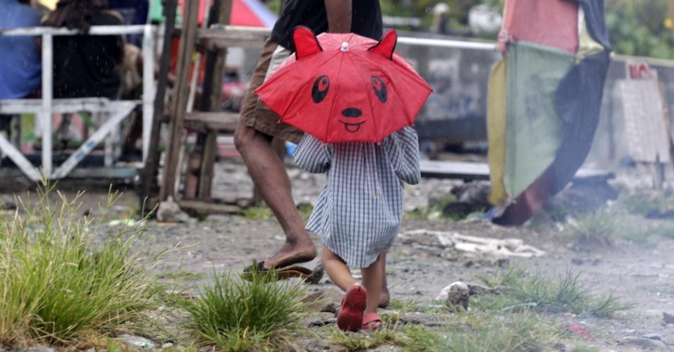 25.out.2012 - Menino filipino usa guarda-chuvas enquanto caminha por rua de Manila, capital das Filipinas, nesta quinta-feira (25). A tormenta tropical Son-Tinh provocou a morte de uma mulher e impediu que 16 mil pessoas se deslocassem pelo país. O governo suspendeu trajetos feitos por mar e pelo ar