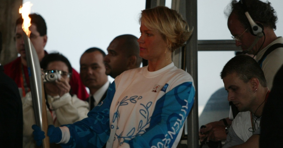 13.jun.2004 - A apresentadora Xuxa Meneguel leva a tocha olímpica no bondinho do Pão de Açúcar