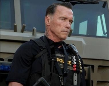 O ator Arnold Schwarzenegger aparece caracterizado como um agente policial no set de filmagens de