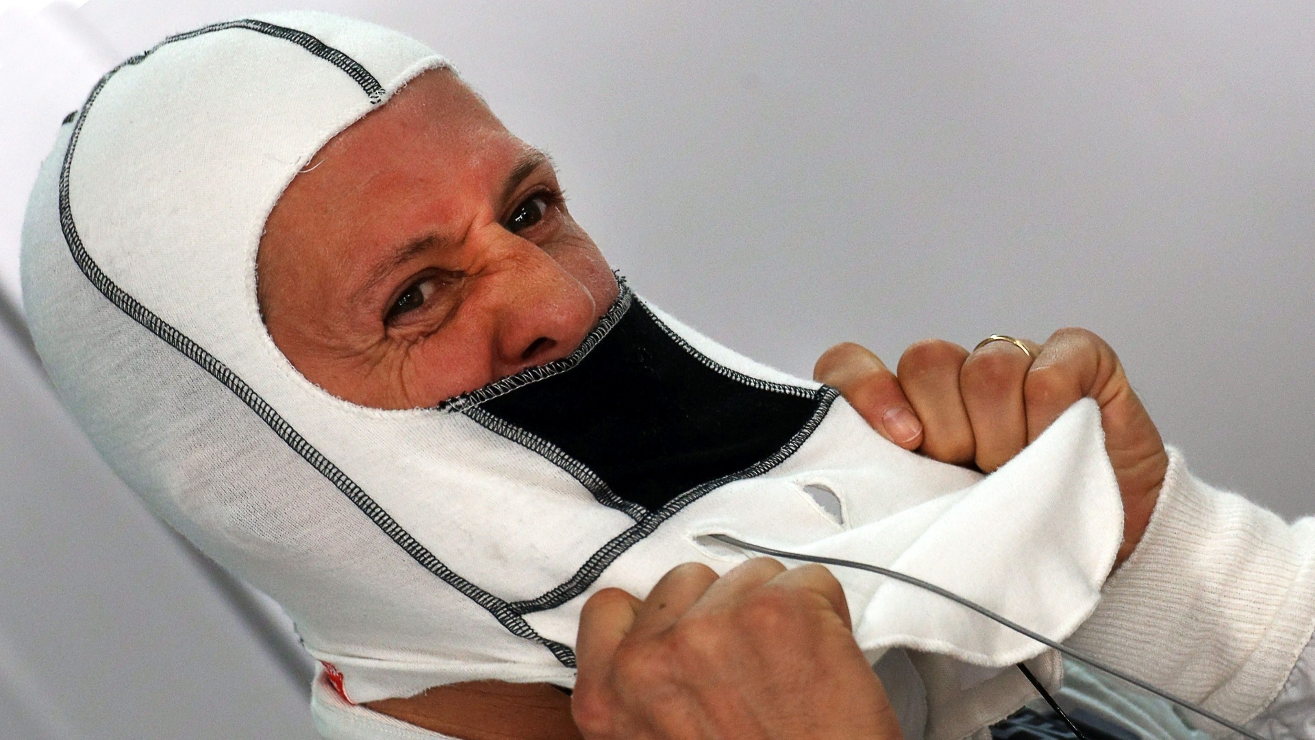 Michael Schumacher ajeita a balaclava da Mercedes antes de ir para a pista no treino do GP da ndia