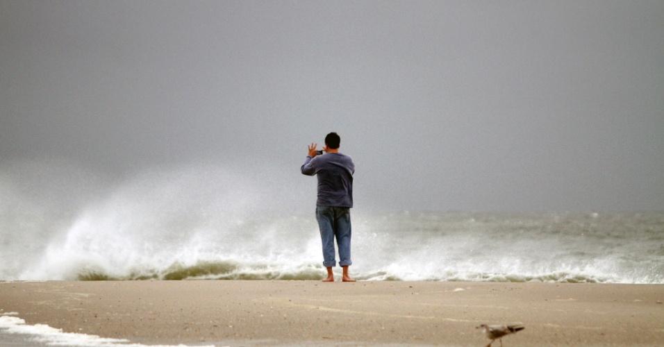 28.out.2012 - Homem fotografa fortes ondas em praia de Cape May, em Nova Jersey, na tarde desta segunda-feira (29). O furacão Sandy, que deve atingir a costa leste dos Estados Unidos ainda nesta segunda-feira, pode afetar cerca de 60 milhões de pessoas, afirmou a empresa United States National Grid, que fornece energia ao país