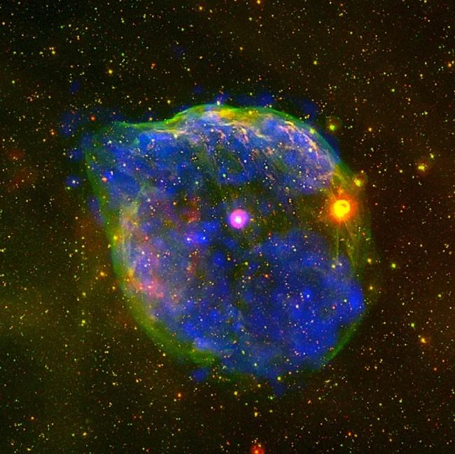 29.out.2012 - A Agência Espacial Europeia (ESA, na sigla em inglês) captou imagens novas - e fantasmagóricas - de uma gigante bolha cósmica a 5.000 anos luz de distância da Terra, na Constelação Cão Maior. Com cerca de 60 anos-luz de diâmetro, o objeto foi formado pelo forte vento soprado de uma estrela massiva, a Wolf-Rayet HD 50896 (ponto rosa no centro). Visíveis apenas em raio X, as marcas azuis representam o plasma quente do sopro estelar e o halo verde surge do choque entre o material ejetado pela estrela e as camadas de gás e poeira no espaço