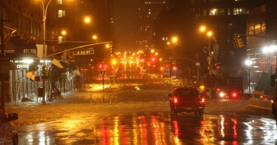29.out.2012 - Carro anda por rua alagada de Manhattan, em Nova York, nos Estados Unidos. As cidades da costa leste do país já sofrem com chuvas e ventos fortes, em razão da aproximação do furacão Sandy. O fenômeno pode afetar cerca de 60 milhões de pessoas, afirmou a empresa United States National Grid, que fornece energia aos Estados Unidos