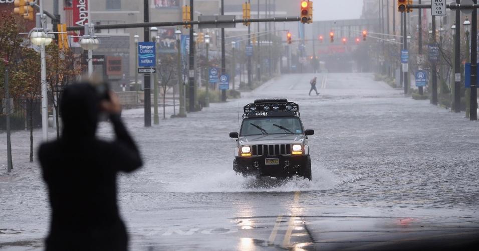 29.out.2012 - Carro passa por rua inundada por fortes chuvas causadas pela passagem do furacão Sandy em Atlantic City, no Estado de Nova Jersey (EUA), nesta segunda-feira (29). O governador do Estado, Chris Christieâ, declarou estado de emergência na cidade, fazendo com que cassinos fossem fechados e 30 mil moradores, evacuados