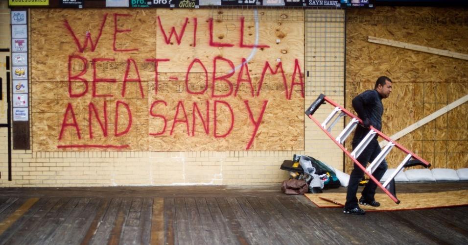 29.out.2012 - Comerciante de Rehoboth Beach, Delaware termina de blindar a loja com chapas de madeira em preparação ao furacão Sandy. Em inglês, escreveu