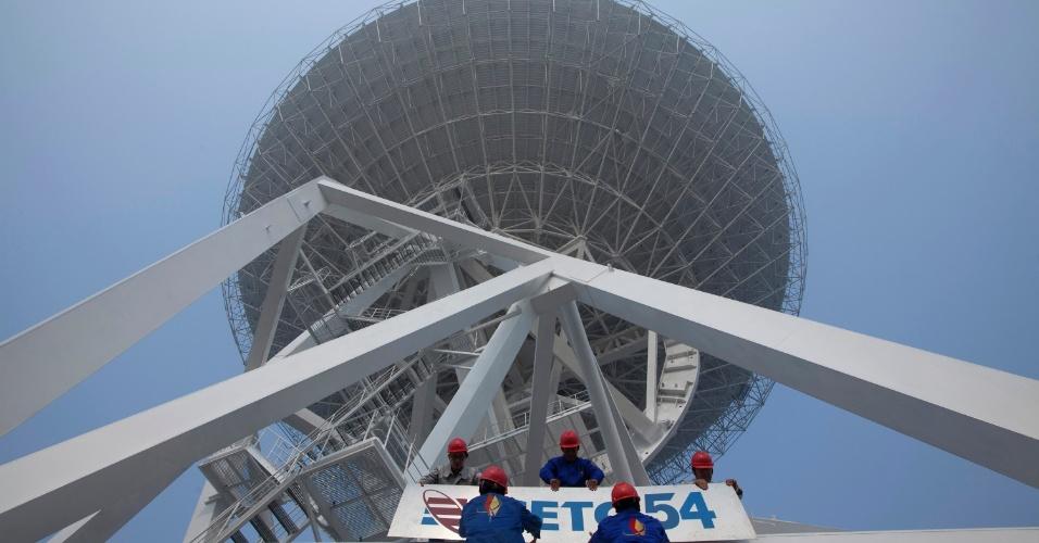 29.out.2012 - Funcionários fixam placas de companhia de tecnologia na base do radiotelescópio recém-construído em Xangai, na China, no último domingo (28). O instrumento de observação espacial tem cerca de 70 metros de altura e pesa mais de 2,65 toneladas