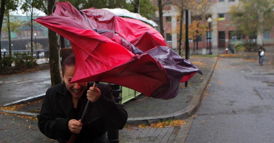 29.out.2012 - Mulher tenta se proteger da chuva enquanto o furacão Sandy se aproxima de Nova Jersey, nesta segunda-feira. Pelo menos 116 mil pessoas em sete Estados americanos estavam sem energia nesta segunda-feira, pouco antes da chegada do furacão ao país, conforme reporta a rede americana CNN