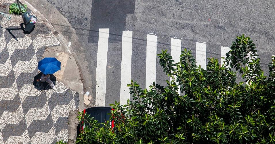 29.out.2012 - Pedestre se protege do sol e calor de mais de 30°C no bairro da Bela Vista, no centro de São Paulo