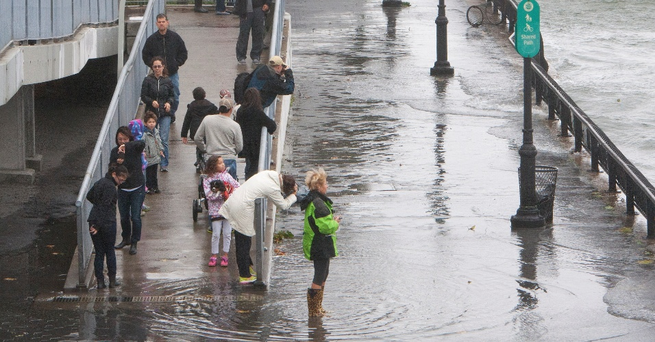 29.out.2012 - Pessoas observam rua inundada na beira da praia de Hampton, no Estado de New Hampshire