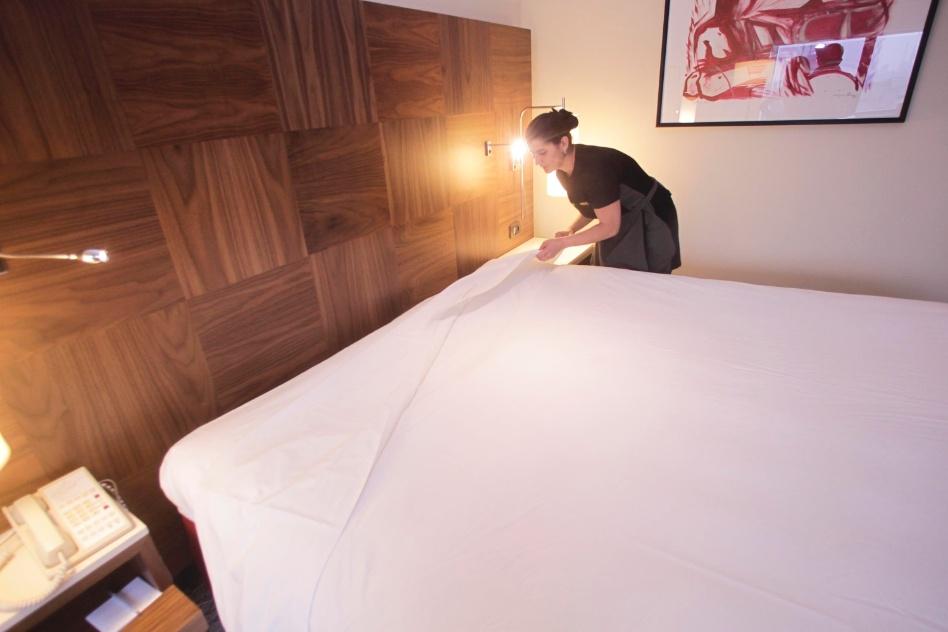 Após estender o edredom ou a colcha sobre a cama, puxe o segundo lençol em direção ao edredom ou à colcha, a uma altura que dê para fazer uma segunda dobra...