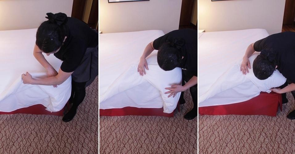 """Depois de colocar, ao pé da cama, as partes soltas do edredom  ou a colcha debaixo da colchão, faça novamente a técnica de """"envelopar"""", como fez com o segundo lençol, agora nas laterais do edredom ou a colcha. Pegue a ponta e a puxe para cima, em um ângulo aproximado de 45º. Assente-a sobre a cama e coloque embaixo do colchão apenas a parte rente à lateral da cama. Em seguida, volte com a ponta do edredom ou a colcha - que está em cima da cama - para baixo, esticando bem a peça"""