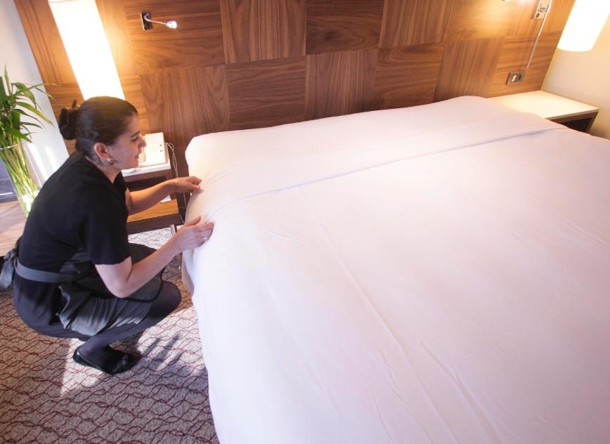 Estique bem a dobra do segundo lençol sobre o edredom ou a colcha