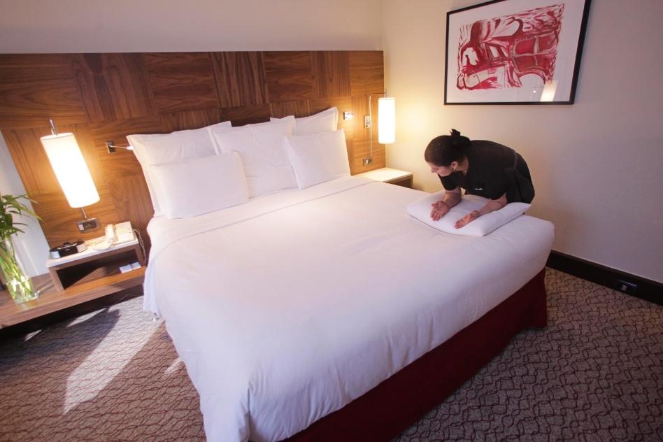 Feitas as dobras do edredom ou da colcha nas laterais da cama, posicione os travesseiros na cabeceira. Para ficarem esteticamente mais bonitos, você pode esticar a espuma dos travesseiros, apertando-a bem com os braços