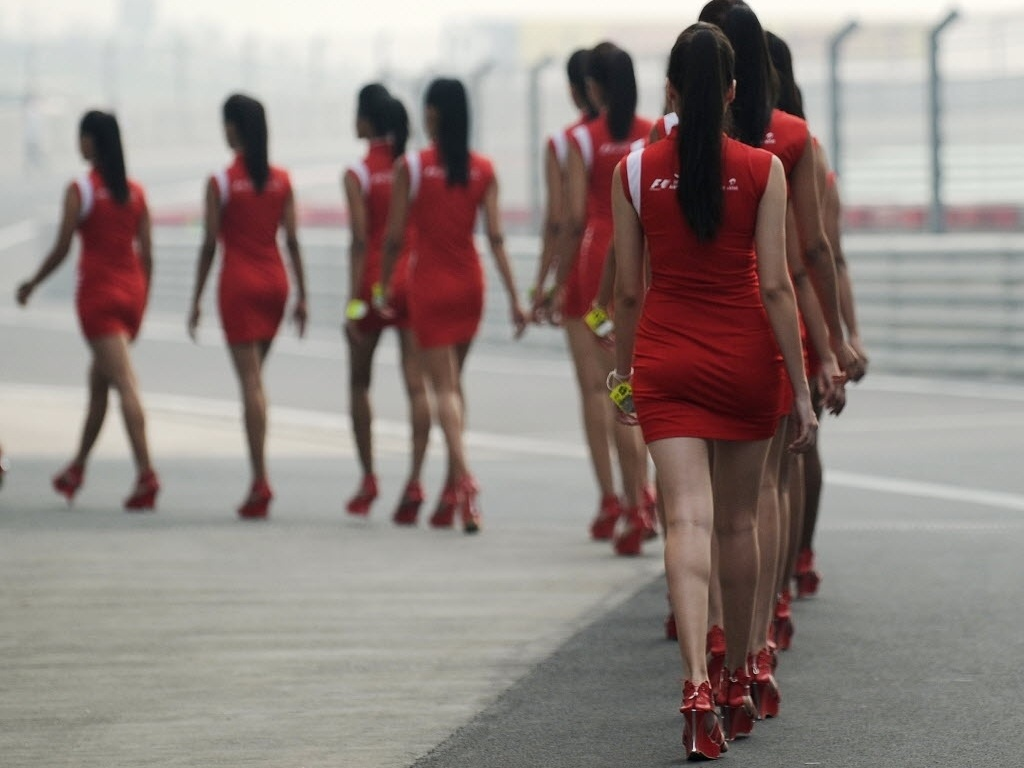 Grid girls desfilam enfileiradas no paddock do GP da ndia