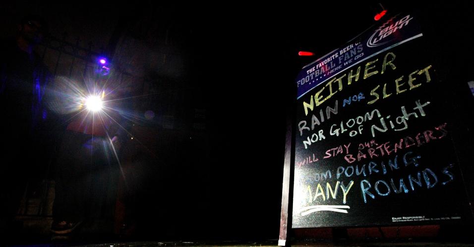 30.out.2012 - Cartaz de bar em Nova York afirma que nem a chuva, nem a neve ('sleet' na verdade é um estágio intermediário entre chuva e neve), nem a escuridão da noite impedirá os garçons de servirem bebidas a vontade. Não há previsão para o abastecimento de energia ser totalmente normalizado na cidade