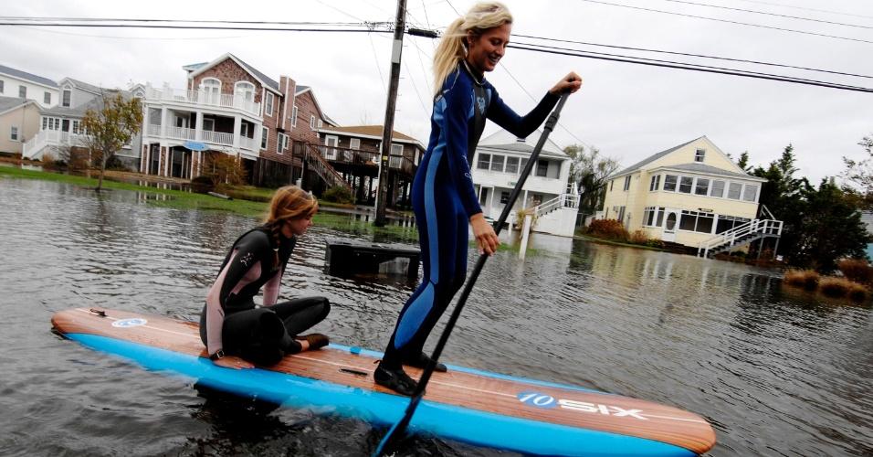 30.out.2012 - Jenna Webb, à esquerda, e Zoe Jurusik se deslocam em uma prancha de paddle board na cidade de Bethany Beach, no Estado de Delaware. Milhões de pessoas ficaram foram afetadas pela mega tempestade Sandy, quando Nova York e uma faixa larga do leste dos Estados Unidos lutaram com inundações e quedas de energia maciços