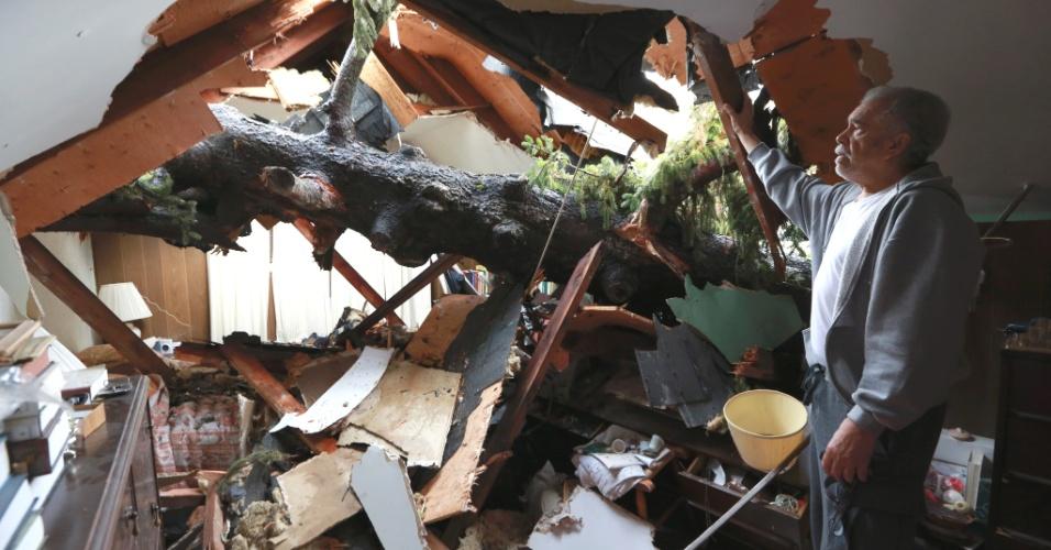 30.out.2012 - Morador observa árvore que caiu em seu quarto, no vilarejo de Ossining, em Nova York, por onde passou o furacão Sandy