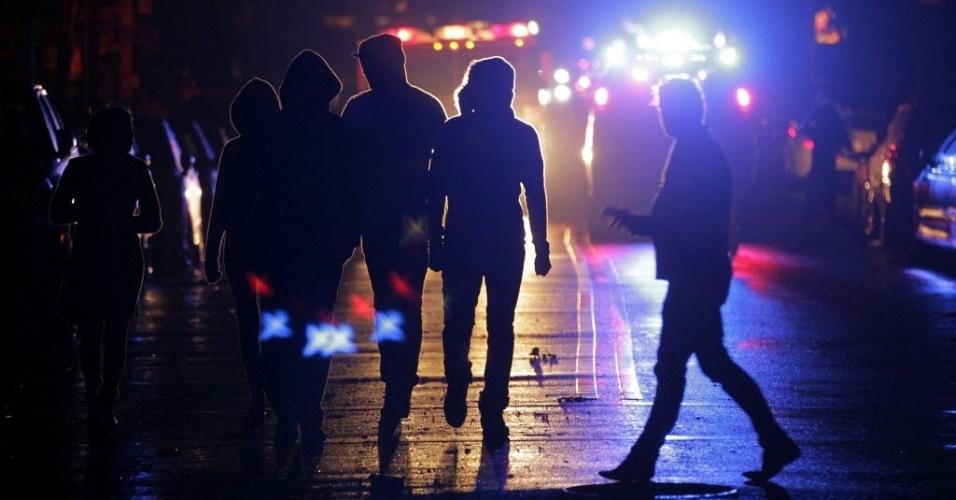 30.out.2012 - Moradores da parte baixa de Nova York circulam por área iluminada por luz do carro de bombeiros