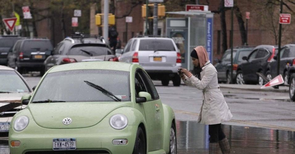 30.out.2012 - Mulher fotografa carro submerso em Nova York, após a passagem do furacão Sandy pela cidade