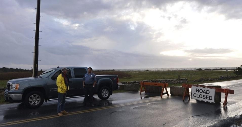30.out.2012 - Policial impede a passagem para o Oceano Atlântico, em área onde postes caíram com a passagem do furacão Sandy, em Westport, Massachusetts (EUA)