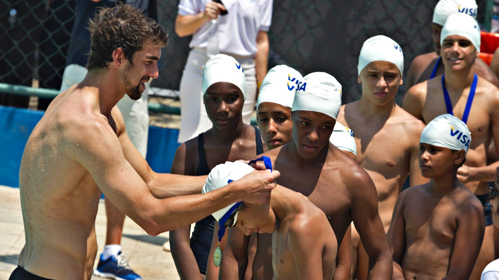 Michael Phelps d medalha para garoto durante visita ao Complexo do Alemo, no Rio de Janeiro (30/10/2012)