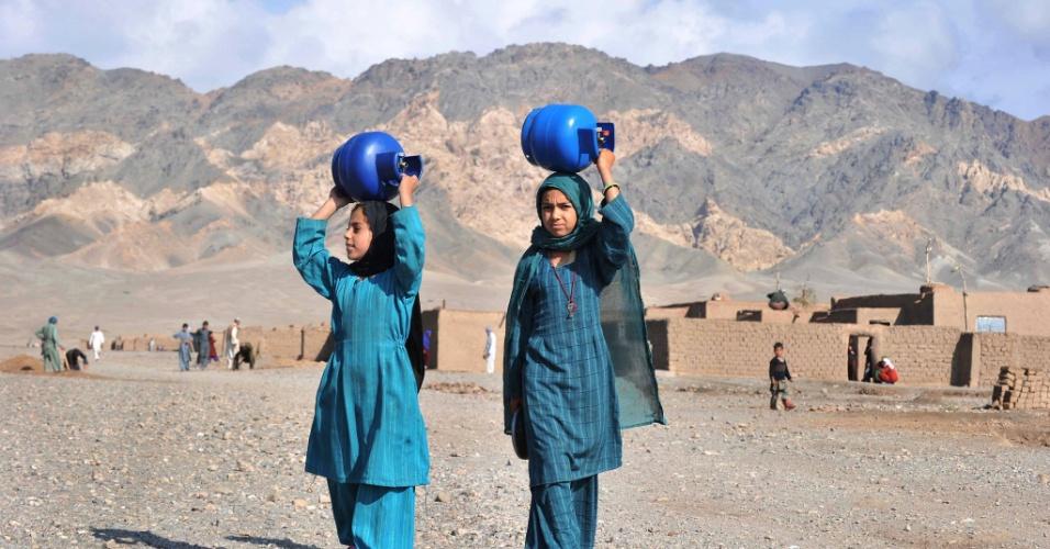 31.out.2012 - Afegãs carregam cilindros de gás na cabeça nos arredores de Herat, no Afeganistão,. Mais de um terço dos afegãos vivem em extrema pobreza, segundo relatório da ONU