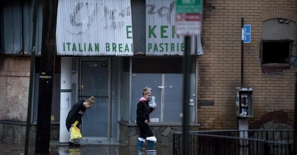 31.out.2012 - Imagem de terça-feira (30) divulgada hoje mostra mulheres caminhando por ruas alagadas da cidade de Hoboken, no Estado americano de Nova Jersey, alagadas após a passagem do furacão Sandy
