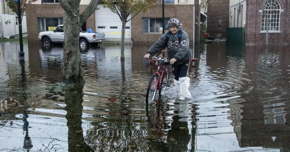 31.out.2012 - Morador anda por ruas alagadas na cidade de Little Ferry, no Estado americano de Nova Jersey. A passagem do furacão Sandy pela região deixou grandes partes da cidade submersas e sem energia elétrica