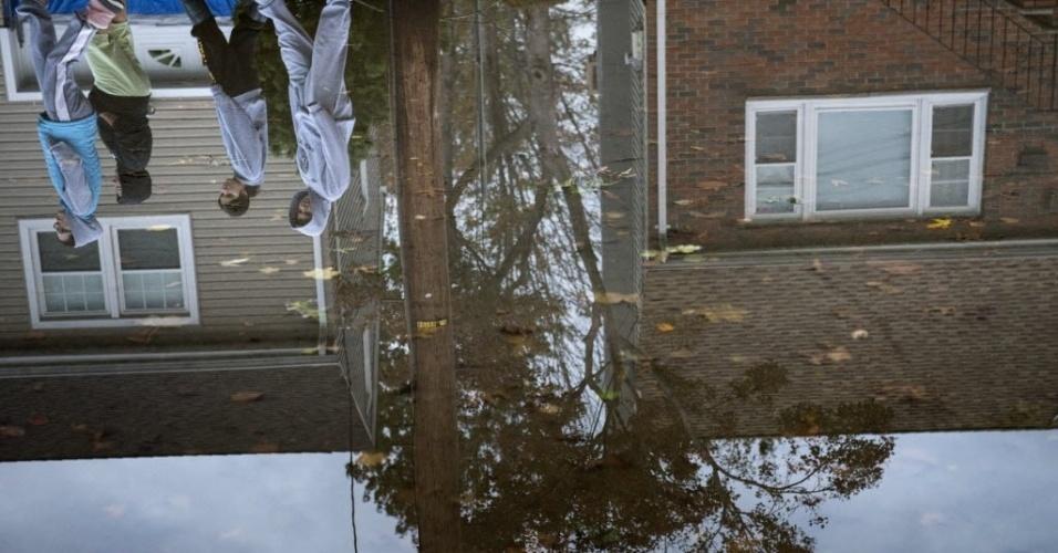 31.out.2012 - Imagem refletida na água mostra moradores andando por ruas alagadas na cidade de Little Ferry, no Estado americano de Nova Jersey. A passagem do furacão Sandy pela região deixou grandes partes da cidade submersas e sem energia elétrica